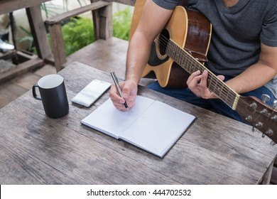 Guitar with man's hand composing music on the wood table at coffee