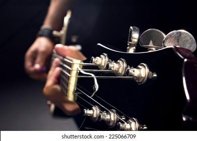 guitar in man's hands, close-up shot, dark background