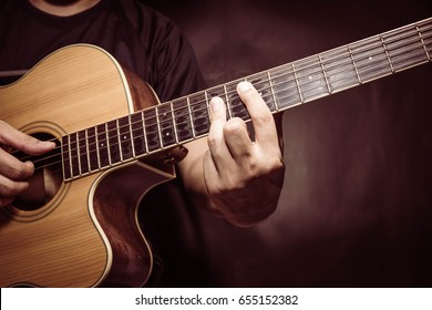 Guitar with a man's hands playing the guitar in the dark background, black space left for the text.