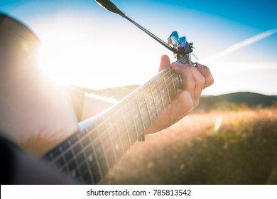 Guitar in the Morning Sun, playing a guitar ontop of a mountain during a music video shoot.