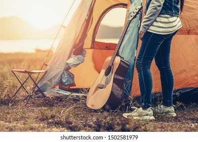 Guitar on the ground near tent at camping with sun light.