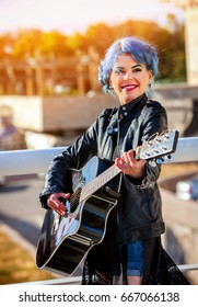 Guitar outdoor music. Woman perform in park outdoor. Girl performing jazz on city street . Spring outside with blue hairstyle background.