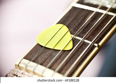 Guitar pick between strings of a fretboard