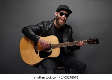 Guitar player with beard and black clothes