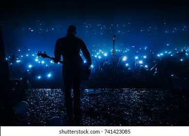 Guitar player in front of crowd on scene in night club. Bright stage lighting, crowded dance floor. Phone lights at concert. Band blue silhouette crowd. People with cell phone lights.