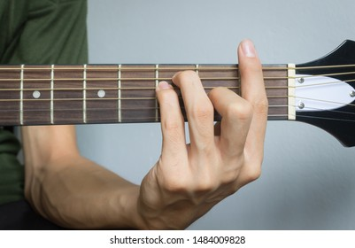 Guitar Player Hand or Musician Hand in F Major Chord on Acoustic Guitar String with soft natural light in close up view