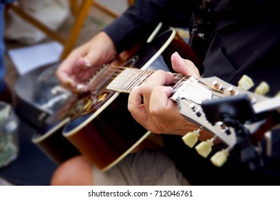 Guitar player holding finger board of instrument with fingers in focus