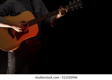 Guitar player on stage. Low light in the dark background
