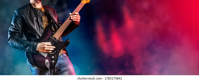 Guitar player performs on stage. Rock guitarist plays solo on an electric guitar. Artist and musician performs like rockstar.
