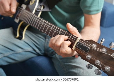 Guitar player playing song indoor closeup
