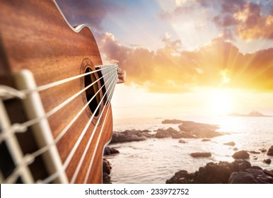 Guitar player at seascape sunset background