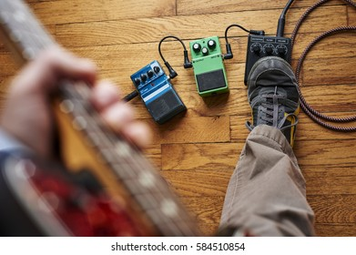 a guitar player, stepping on an effect pedal