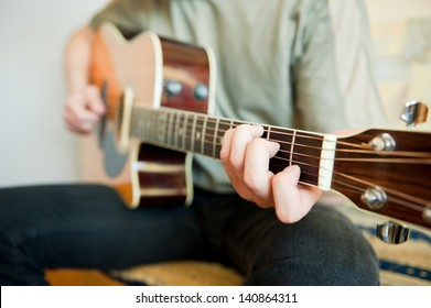 Guitar player - Young man playing acoustic guitar in his room.