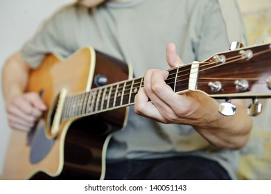 Guitar player/Young man playing the acoustic guitar/focus on his left hand.