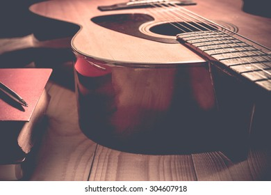 Guitar with Red Book and pen on a wooden table, Vintage style.