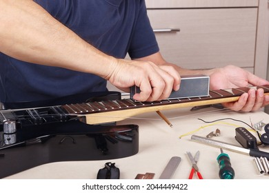 Guitar repairer aligns the frets on guitar neck with leveling bar.