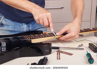 Guitar repairer burnishes the edge of frets on neck of the electric guitar.