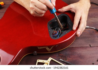 Guitar repairer soldering electric guitar electronics in his workplace.