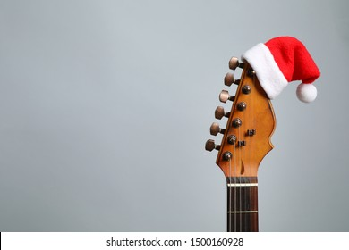 Guitar with Santa hat on grey background, space for text. Christmas music