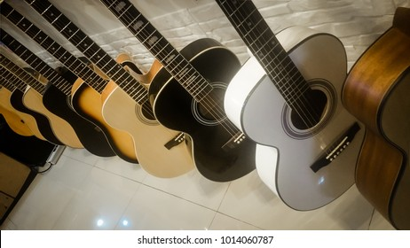 Guitar shop concept . acoustic guitar and Ukulele on display for sale hanging in a music store .