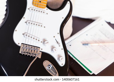 Guitar songwriting at home. Notepad and pencil with electric guitar close up