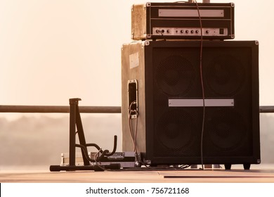 Guitar stand with amplifier system standing on evening open air stage.