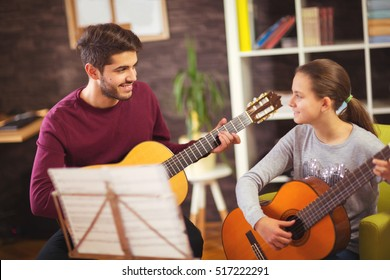 Guitar teacher teaching the little girl