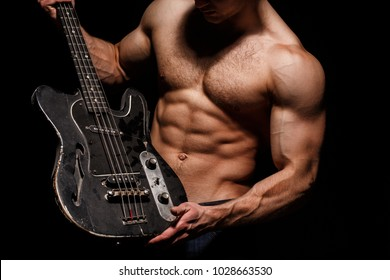 Guitar. Torso man. Play the guitar. Chest muscles, Six pack, ab, triceps. Music festival. Instrument on stage and band. Strong, muscular, muscles man, bodybuilding. Music concept. Electric guitar.