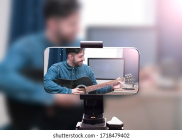 Guitar tutorial with smartphone. Screenshot inside the music course. Technology and leisure. Teacher teaching how to play an instrument. Mobile screen recording online music at home.