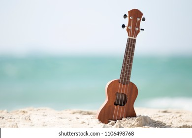 Guitar ukulele on sand beach with clear water and blue sky. The beautiful summer beach wiht copy space. Music make a happy and luxury in holiday summer background. Travel and lifestyle Concept.