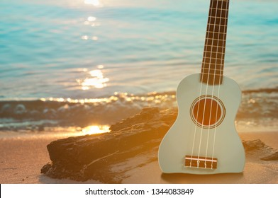 Guitar ukulele on sand beach with clear water and blue sky. Travel and lifestyle Concept.