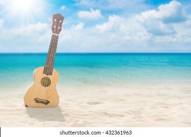 guitar ukulele on sand beach with bright sun