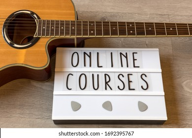 """Guitar and whiteboard with text """"online courses"""" to exemplify online guitar lessons."""