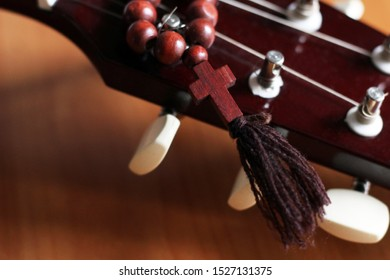 Guitar and wooden cross, music and religion, so close