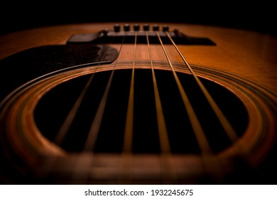 Guitar.Guitar's chords.Acoustic guitar.Music.Music background.Image of an acoustic guitar in the dark.Playing music with some friends in the dark.Classical music.Closeup image of an acoustic guitar.
