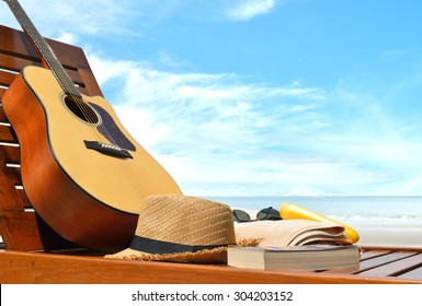 Guitar,hat,book and beach accessories on a beach chair with sea background