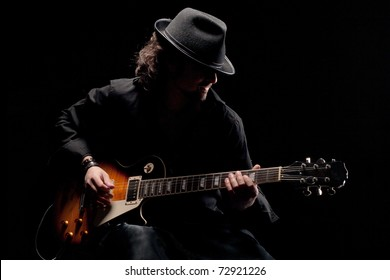 Guitarist in black hat playing guitar