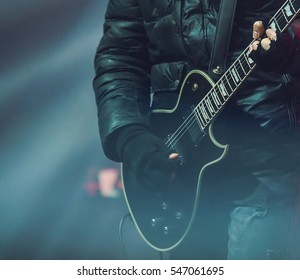 Guitarist in black playing on black guitar on concert