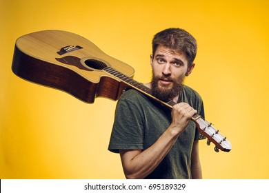 Guitarist with a guitar on a yellow background, music, musical instrument