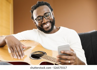 Guitarist with guitar using mobile in his home.