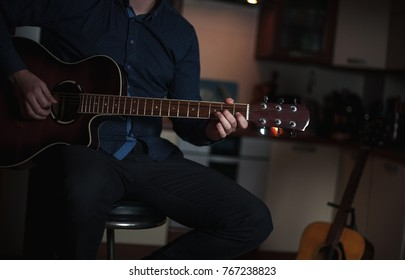 The Guitarist Guy plays the guitar in a bar in a beautiful setting on a high bar stool