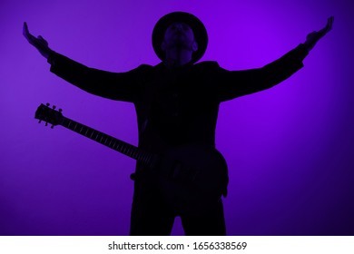 guitarist in a hat is standing with his arms outstretched on a blue background