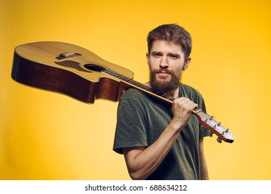 Guitarist holding a guitar on his shoulder on a yellow background