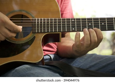 A guitarist holding a Guitar playing the instrument in a guitar lesson. Close up on hands of person on guitar strings.