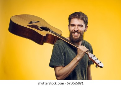 Guitarist holding a musical instrument on his shoulder on a yellow background