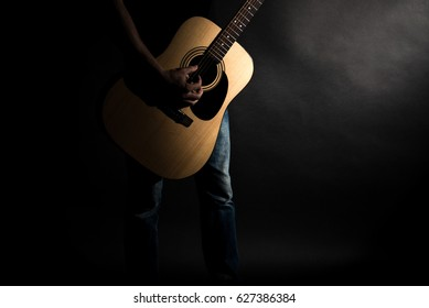 The guitarist in jeans plays an acoustic guitar, on the left side of the frame, on a black background