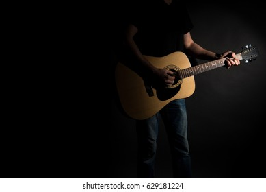 The guitarist in jeans plays an acoustic guitar, on the right side of the frame, on a black background