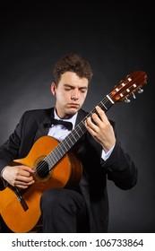 Guitarist. Man playing guitar on black background