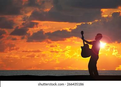 Guitarist man playing guitar at sunset with the sunlight bursting around him