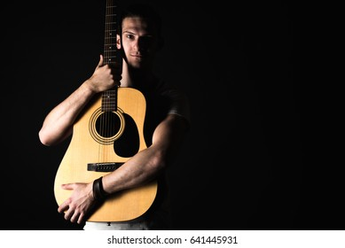 Guitarist, music. A young man stands with an acoustic guitar on a black isolated background